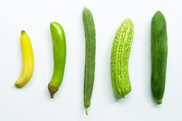 Banana, melanzana lunga verde, luffa acutangula, melone amaro, papaya verde su bianco