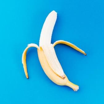 Banana ripulito dalla buccia su una superficie luminosa