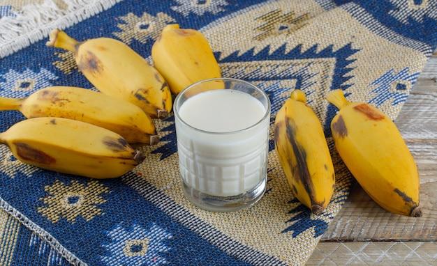 Banane con vista ad alto angolo di latte sul tappeto in legno e kilim