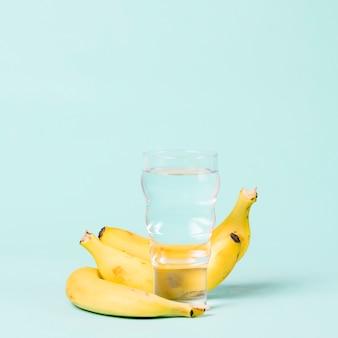 Banane e bicchiere d'acqua copiano lo spazio