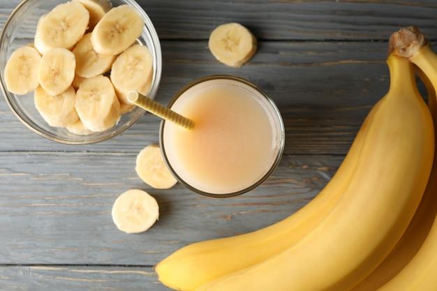 Banane e succo sulla tavola di legno, vista superiore