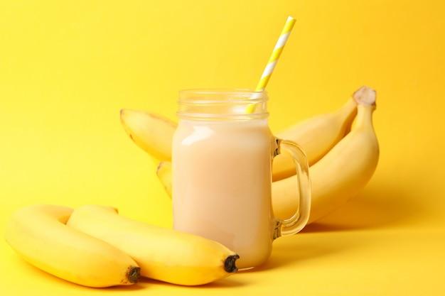 Banane e succo sulla tavola gialla. frutta fresca
