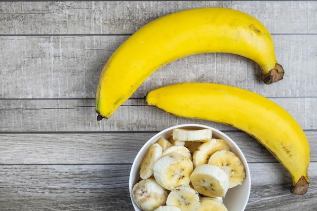 Banane fresche e banane tagliate a pezzi in una ciotola per la salute sul tavolo.