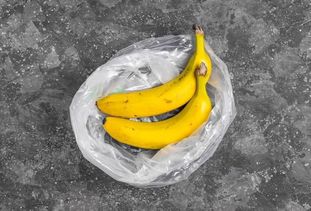Banane in un sacchetto di plastica trasparente su uno sfondo grigio