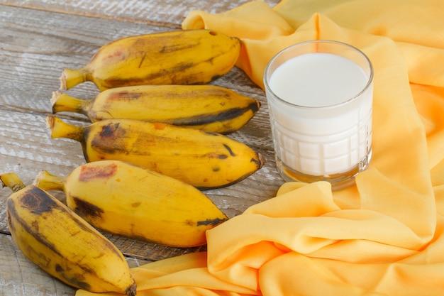 Banane mature con latte su legno e tessile, ad alto angolo di visione.