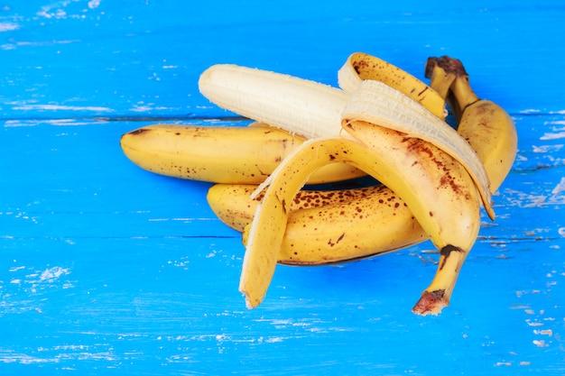 Banane mature sul vecchio tavolo in legno verniciato blu