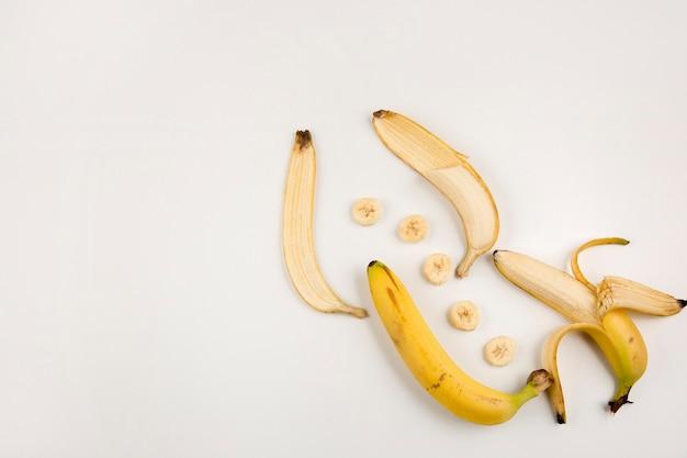 Banane sbucciate e affettate su sfondo bianco nell'angolo