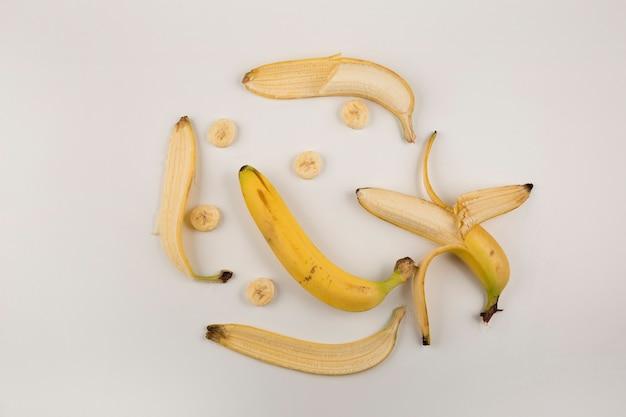 Banane sbucciate e affettate su sfondo bianco, vista dall'alto