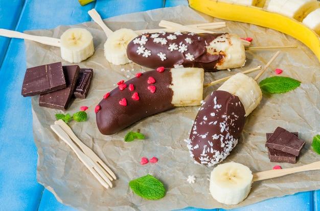 Banane surgelate fatte in casa ricoperte di glassa al cioccolato. dessert delizioso, dietetico e sano.