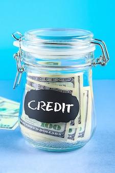Banca con dollari, calcolatrice su grigio. finanza, salvadanaio, conservazione, credito.