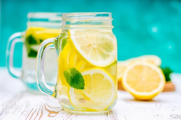 Banche con maniglie con limonata fredda su un fondo di legno bianco. limoni.