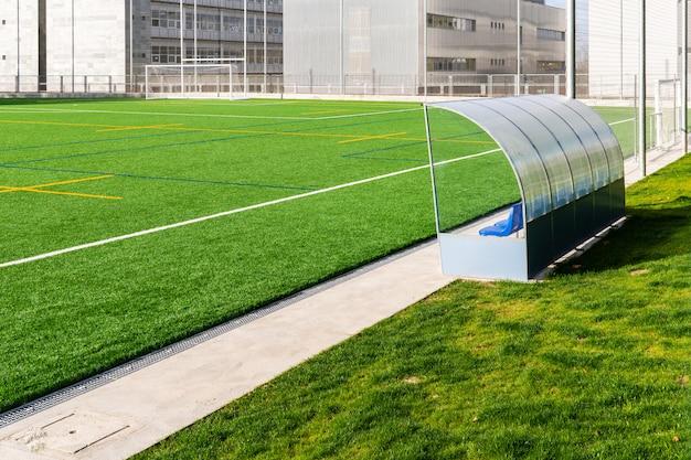 Banco di calcio di un campo da calcio con erba sintetica