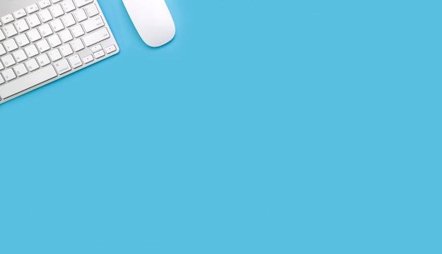 Banco di lavoro dell'area di lavoro con il computer portatile sul blu