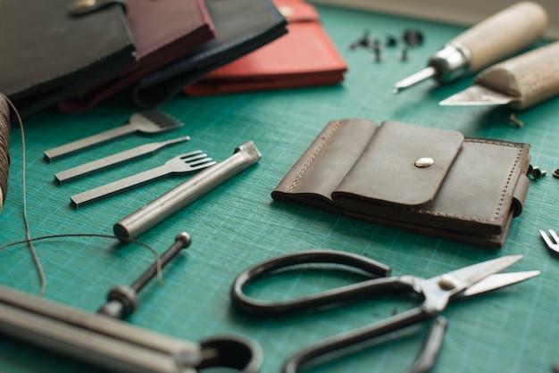 Banco di lavoro di leathersmith. utensili da lavoro in pelle su un tavolo da lavoro