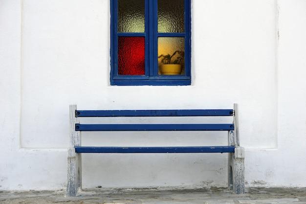 Banco di legno blu sotto la bella cornice della finestra blu sulla parete bianca