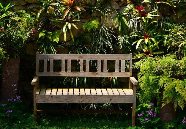 Banco di legno nel giardino un giorno soleggiato con la priorità bassa dell'albero
