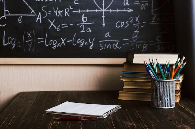 Banco di scuola in aula, con libri sullo sfondo del bordo di gesso con formule scritte
