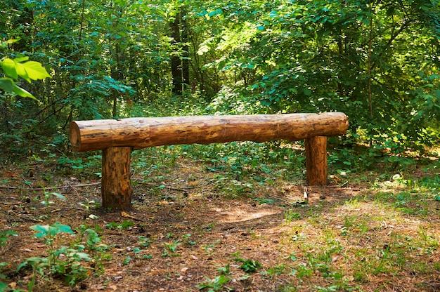 Banco di tronchi di legno per le persone nella foresta verde.