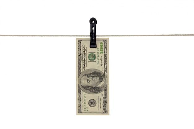 Banconota americana da 100 dollari in una corda da bucato - riciclaggio di denaro sporco - concetto sporco dei soldi - isolato
