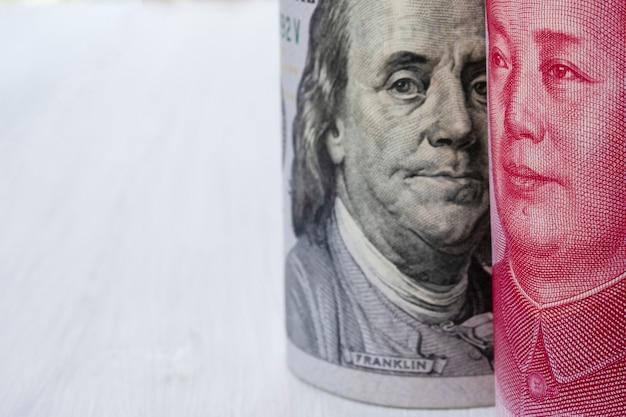 Banconota del dollaro americano e della cina yuan su fondo bianco.