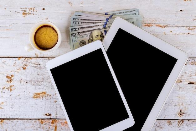 Banconota e tazza di caffè del dollaro americano con gli articoli per ufficio finanziari della compressa digitale
