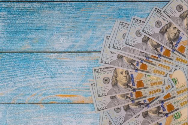Banconota in dollari degli stati uniti 100 su legno blu.