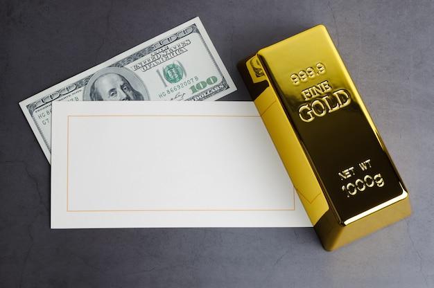 Banconota in dollari e cartolina d'auguri del lingotto del lingotto della barra di oro.