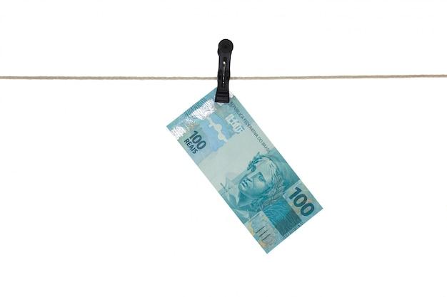 Banconota reale brasiliana 100 in una corda da bucato - riciclaggio di denaro sporco - concetto sporco dei soldi - isolato