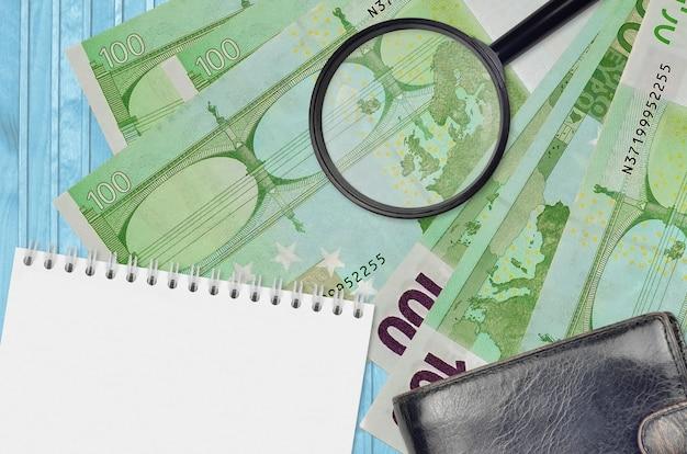 Banconote da 100 euro e lente d'ingrandimento con borsa nera e blocco note