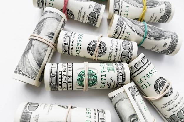 Banconote da cento dollari americani arrotolate come un tubulo.
