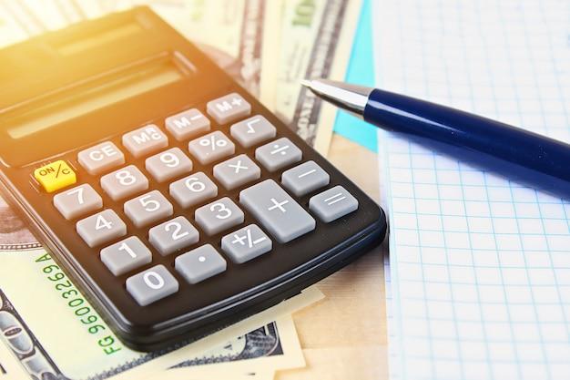 Banconote da cento dollari degli stati uniti, calcolatrice, fatture.