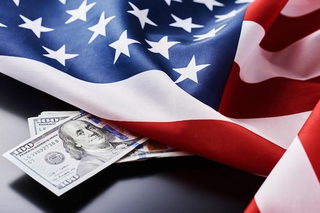 Banconote dei soldi dei usd di valuta e della bandiera nazionale di usa su un fondo scuro.
