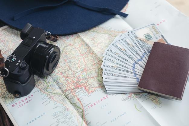 Banconote del dollaro, carta di credito, passaporto, macchina fotografica e cappello blu