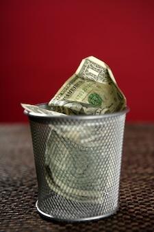 Banconote del dollaro sul cestino