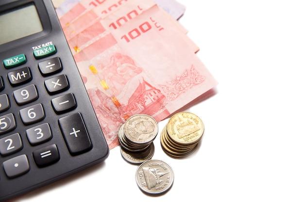 Banconote e calcolatrice tailandesi su spazio bianco