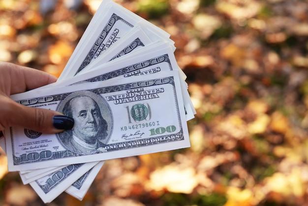 Banconote in denaro cento dollari nella mano di una ragazza