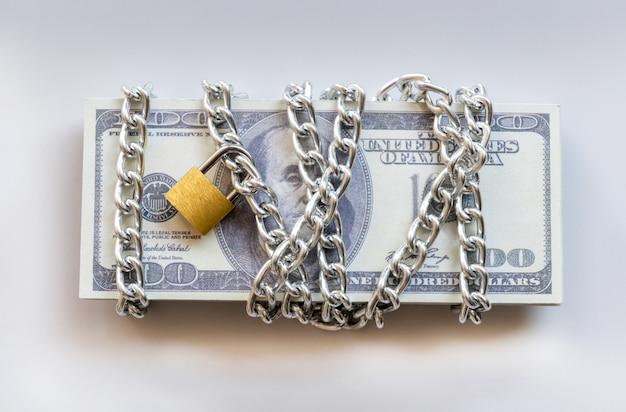 Banconote in dollari con catena e lucchetto, denaro di sicurezza e concetto di investimento.