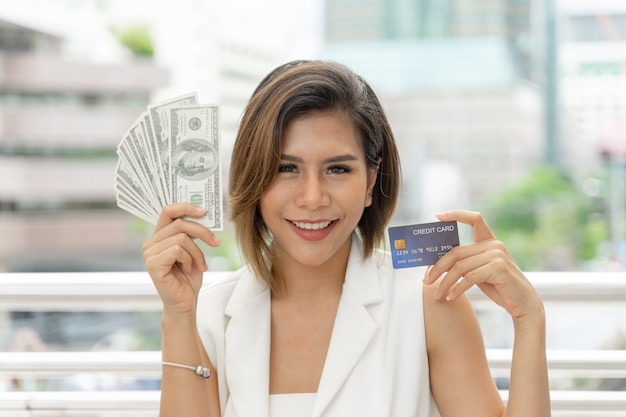Banconote in dollari e carta di credito asiatiche riuscite della bella donna di affari della tenuta della donna di affari disponibili