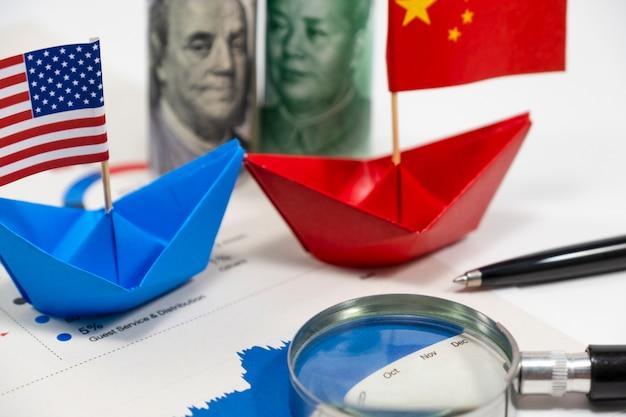 Banconote in dollari usa di stati uniti d'america e yuan china con bandiera sulla nave con r finanziaria