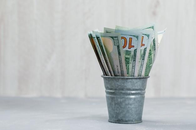 Banconote in mini secchio su gesso e tavolo in legno