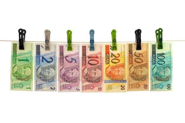 Banconote reali brasiliane in una corda da bucato - riciclaggio di denaro sporco - concetto sporco dei soldi - isolato