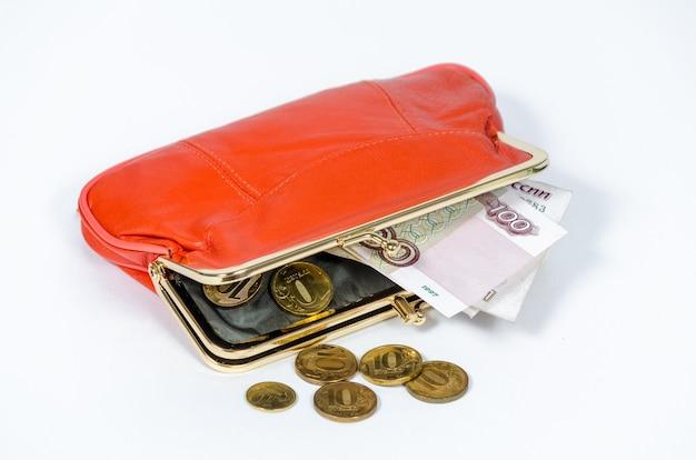 Banconote russe da cento rubli e monete da dieci rubli giacciono in una borsa da donna arancione