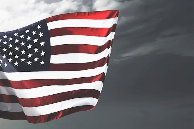 Bandiera americana che fluttua nell'aria con un cielo drammatico