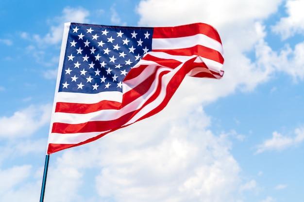 Bandiera americana che ondeggia nel vento contro il cielo blu