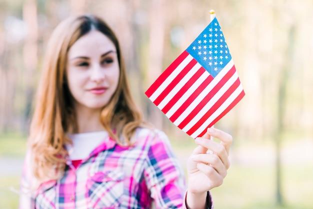 Bandiera americana sorridente della tenuta femminile