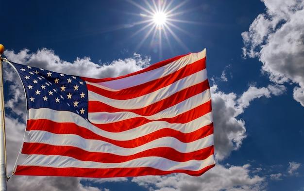 Bandiera americana su un post con sfondo nuvoloso