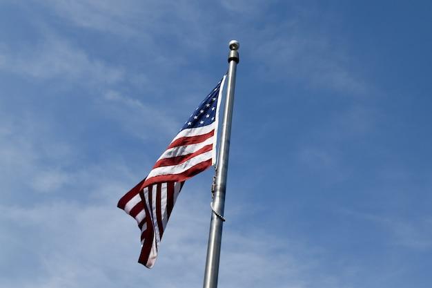 Bandiera americana vicino agli alberi sotto un cielo nuvoloso e una luce solare blu