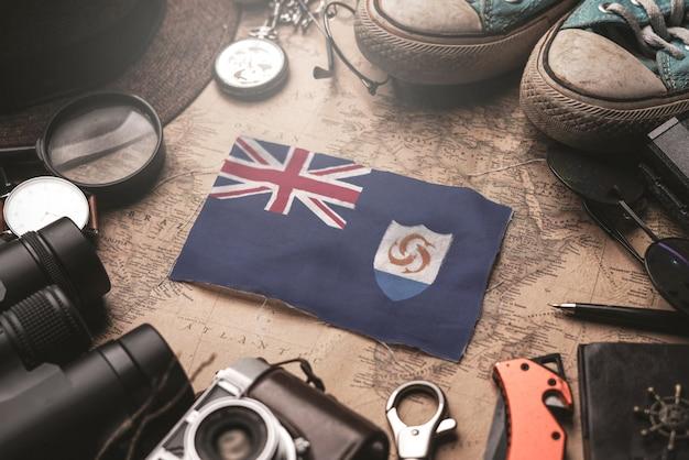 Bandiera anguilla tra gli accessori del viaggiatore sulla vecchia mappa vintage. concetto di destinazione turistica.