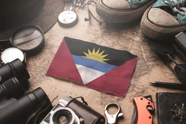 Bandiera antigua e barbuda tra gli accessori del viaggiatore sulla vecchia mappa vintage. concetto di destinazione turistica.