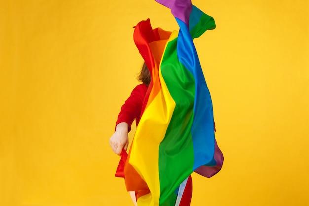 Bandiera arcobaleno. donna che tiene e sventola grande bandiera lgbt